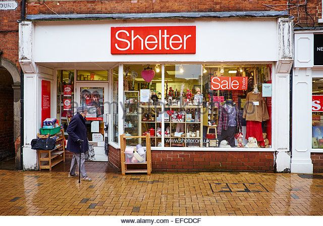 Elderly Woman Walking Past The Shelter Charity Shop High Street Rugby Warwickshire UK - Stock Image