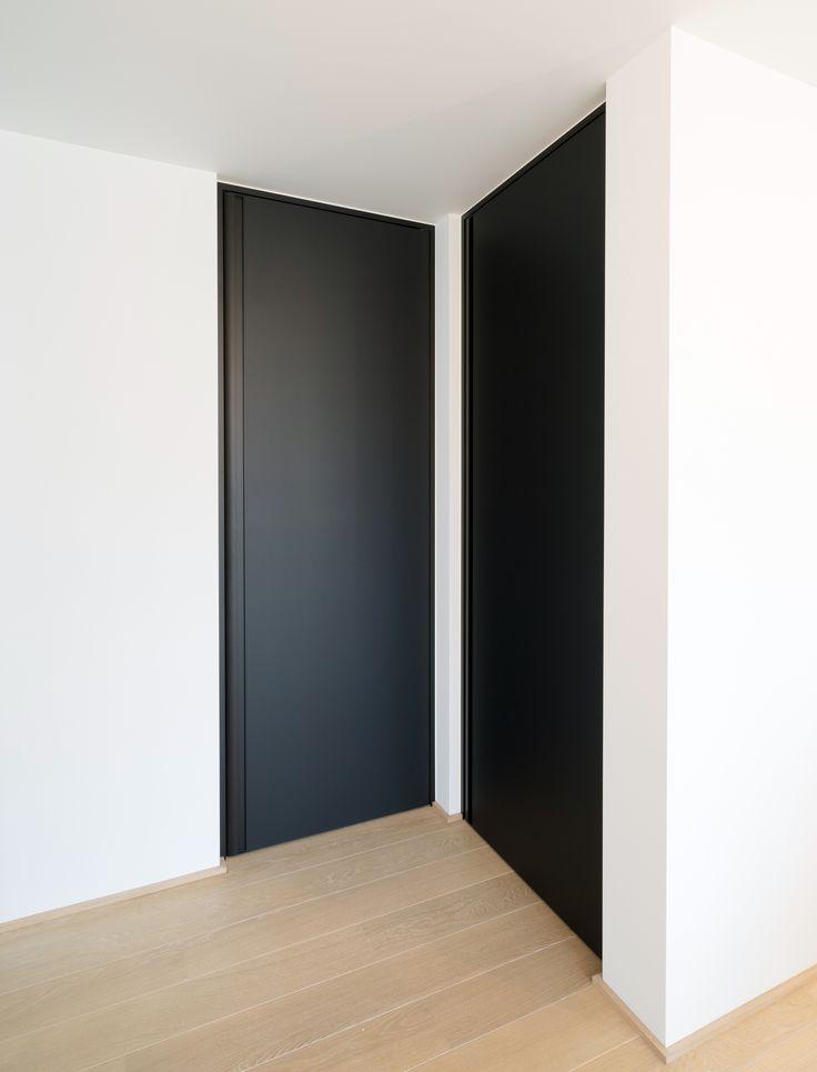 Zwarte deuren van vloer tot plafond, volledig op maat gemaakt door Anyway Doors met een zwarte blokkader en een verticale inbouwgreep. De verticale greep maakt de deur praktisch naar kinderen toe en zorgt ervoor dat de deur geen uitstekende elementen heeft waardoor de muur niet beschadigd kan worden. #zwartedeuren #zwartebinnendeur
