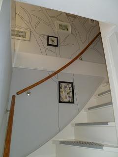 Een zelfgemaakte muurschildering van een boom bij de trap opgang. Fotolijstjes (Ikea) in zwart, aluminium en wit. Sommigen met tekst, anderen met stukje stof.
