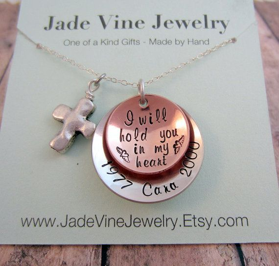 """This necklace is a great alternative to a traditional sympathy gift. The recipient can keep this forever and will be able to feel some comfort while wearing it. The phrase on this necklace says, """" I will hold you in my heart"""" and has two small hearts with angel wings on each side. This can be symbolic for any loved one but might closely relate to the loss of a child or infant. The necklace comes with a small cross charm and is personalized with the birth year, name of loved one, and death…"""