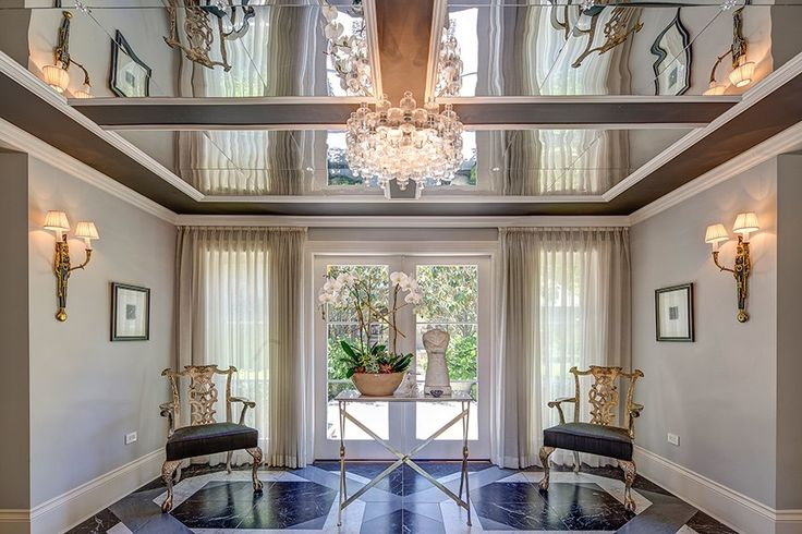 The entry in the main house features graphic marble floors and a mirrored ceiling.