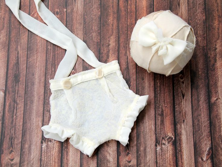Cream Set of 2 pieces.Newborn shorties made of cream tulle with floral print adorned with 2 buttons on the waist and cream chiffon veil belt.The shorties have 2 chiffon veil straps which ties on the back. The tieback is made of cream tulle and chiffon veil ribbon.