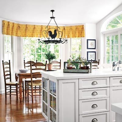 The island of this kid-friendly kitchen is capped by a cabinet with clear plastic fronts so that the children can safely set their own places at the table. | Photo: Tria Giovan | thisoldhouse.com
