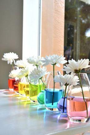 Tischdeko Idee für eine Gartenparty oder eine Sommerparty – oder einen Regenbogen Kindergeburtstag. Einfach unterschiedliche Glasgefäße in einer Linie aufstellen, das Wasser mit Lebensmittelfarbe einfärben und einzelne weiße Blumen reinstellen.