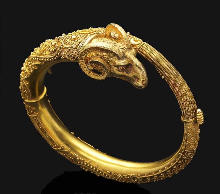 An antique Byzantine revival gold bangle, circa 1880 Of hinged design and oriental inspiration, the textured gold ram's head terminal to the highly decorated band of bead and ropetwist detail, mounted in yellow gold, some beads deficient, weighing 44.3 grams total, inner circumference 16.8cm