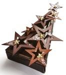 """Une autre création signée La Maison du Chocolat: la """"Bûche Constellation"""". Celle-ci est composé d'étoiles au chocolat noir et au lait, d'une mousse au chocolat noir de République Dominicaine, d'une génoise de cacao, d'une ganache de chocolat au lait au caramel et de fines feuilles craquantes au chocolat noir. Les chocolatiers y ont également incorporé du jus et des zestes de clémentines de Corse. De petites étoiles recouvertes de feuilles d'or viennent décorer le tout."""