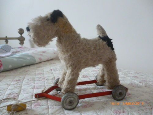 VINTAGE DOG ON WHEELS,FOX TERRIER.PULL ALONG PUSH ALONG.STUFFED TOY DOG | eBay. He's an expensive little guy :)