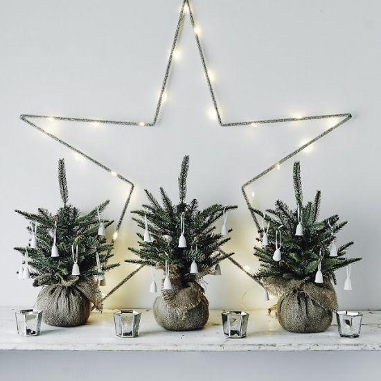 małe choinki w jutowych woreczkach i duża gwiazda z ledowymi lampkami na ścianę do małego pokoju - Lovingit.pl