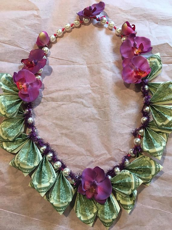 Orchid Fishtail and Pearl Money leis, simple yet gorgeous 10-$2 bills or 20 $1 US dollars bills folded into fishtail accented with Pearls. About 30long end to end. This lei takes 2.5 hours to fold plus 1.5 hour to construct, so if the graduate decides to spent the money, they can and still have a lei of peals to wear. We also mail it in a shape of flower