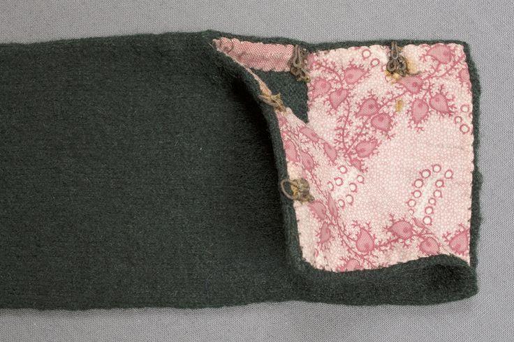 Spedetröja i mörkgrönt ullgarn.  Tröjan är slätstickad med ett 20 mm brett parti i nederkanten i rätstickning. Litet sprund i sidorna.  Ärmsprundet är75 mm långt, det hålls ihop av två hyskor och hakar.  Invändigt är halsringningen kantad med en röd och vit ca 10 mm bred tygremsa. Ärmen är fodrad nedtill, 50 mm, med ett tryckt bomullstyg i rött, rosa och vitt.  Kant- och foderremsor är påsydda för hand. Tröjan är valkad.   Masktäthet/cm: ca 6 maskor på höjden och bredden.  Axelbredd: 80 mm…
