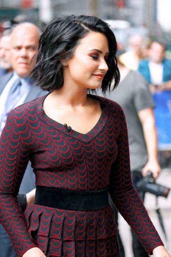 carré ondulé, demi lovato, coupe femme courte avec de boucles légères sur des cheveux noircis, robe stylée