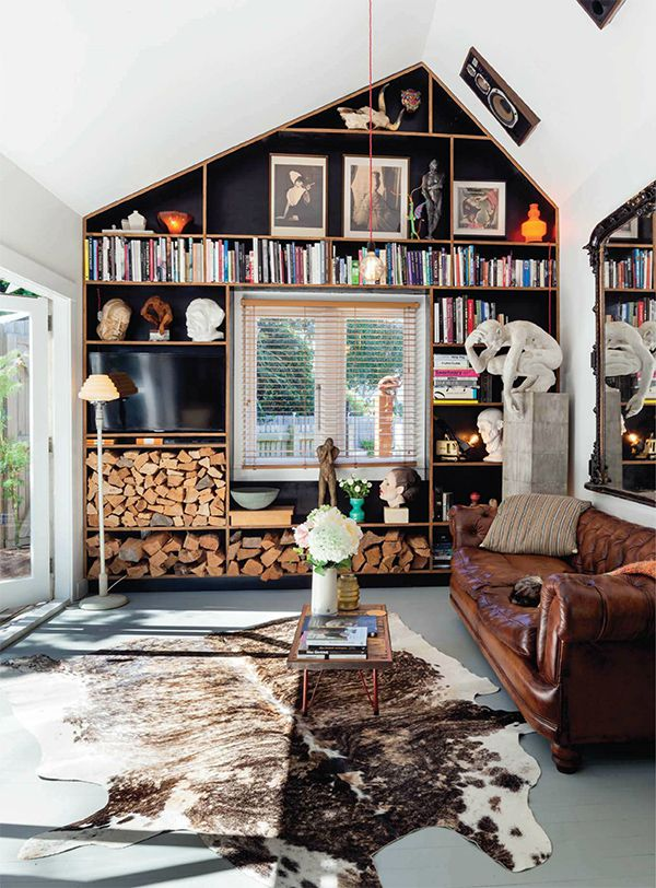Worn leather tufted sofa, framed vintage artwork, colorful books, natural wood, cowhide, & a statue. Everything you could want in a room.