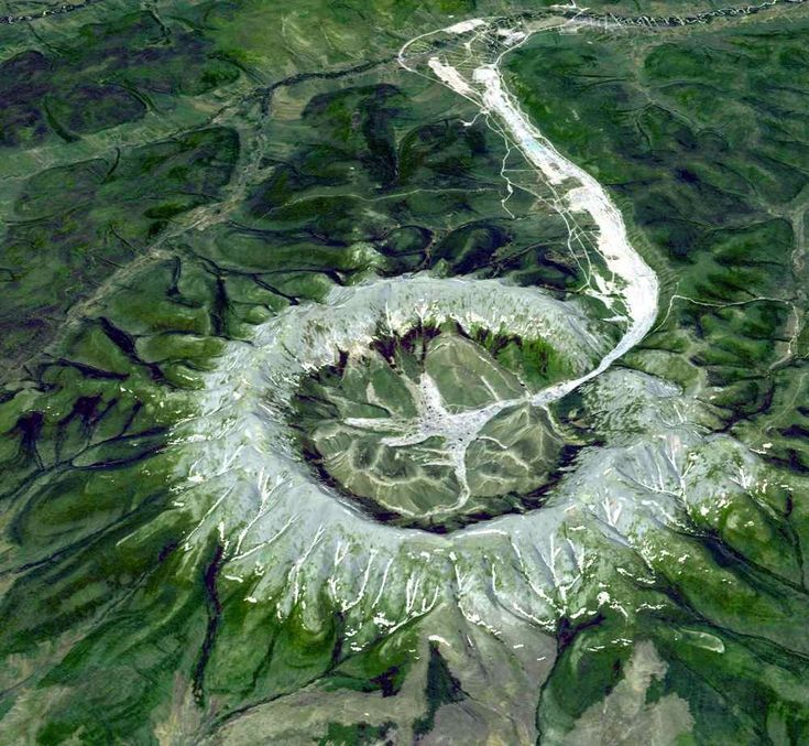 This is neither an impact crater nor a volcano. It is a perfect circular intrusion, about 10 km in diameter with a topographic ridge up to 600 m high. The Kondyor Massif is located in Eastern Siberia, Russia, north of the city of Khabarovsk. It is a rare form of igneous intrusion called alkaline-ultrabasic massif and it is full of rare minerals