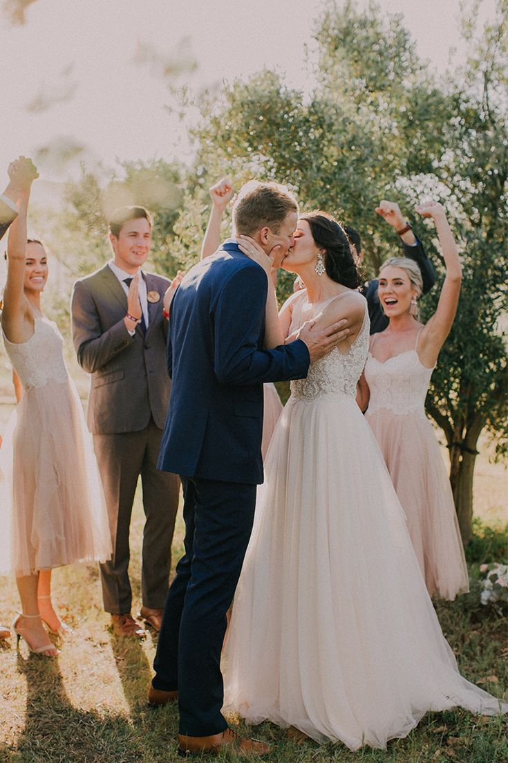 Add some fun to your wedding photos by having your bridal party in the background and trying some more relaxed poses.