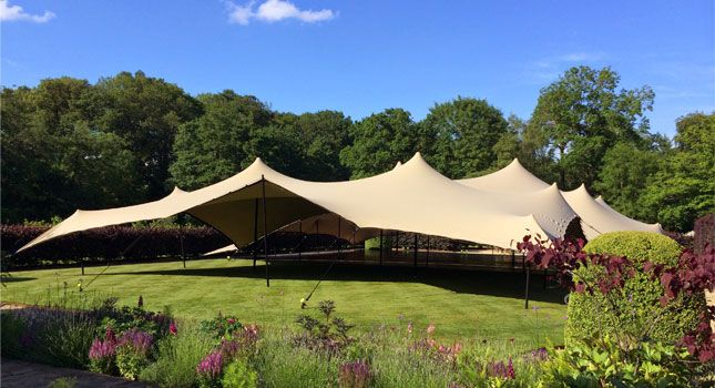 A linked chino stretch tent set up and ready for its guests at this outdoor event.
