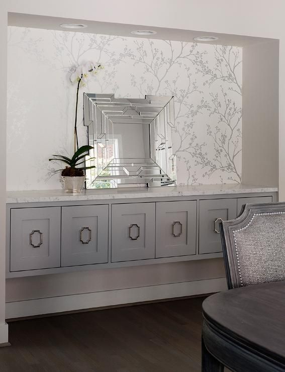 A dining Room nook is clad in Schumacher Twiggy Silver Wallpaper lined with leaning fretwork mirror placed on a long gray floating buffet cabinet adorned with drop pulls.