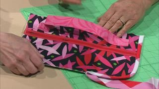 Travel Gear Made Easy, Part 1 Video from Sewing with Nancy. Organize and tote your valuables for vacation, shopping, and work with quick and classy gear. Nancy's guest, Mary Mulari, has designed unique travel accessories that are clever and trendy. She and Nancy show how to make a roll-up blanket, easy zipper pulls, a roomy fold-up tote, a tray for gathering travel supplies, and much more. Organize your stuff so you can kick back and enjoy the ride!