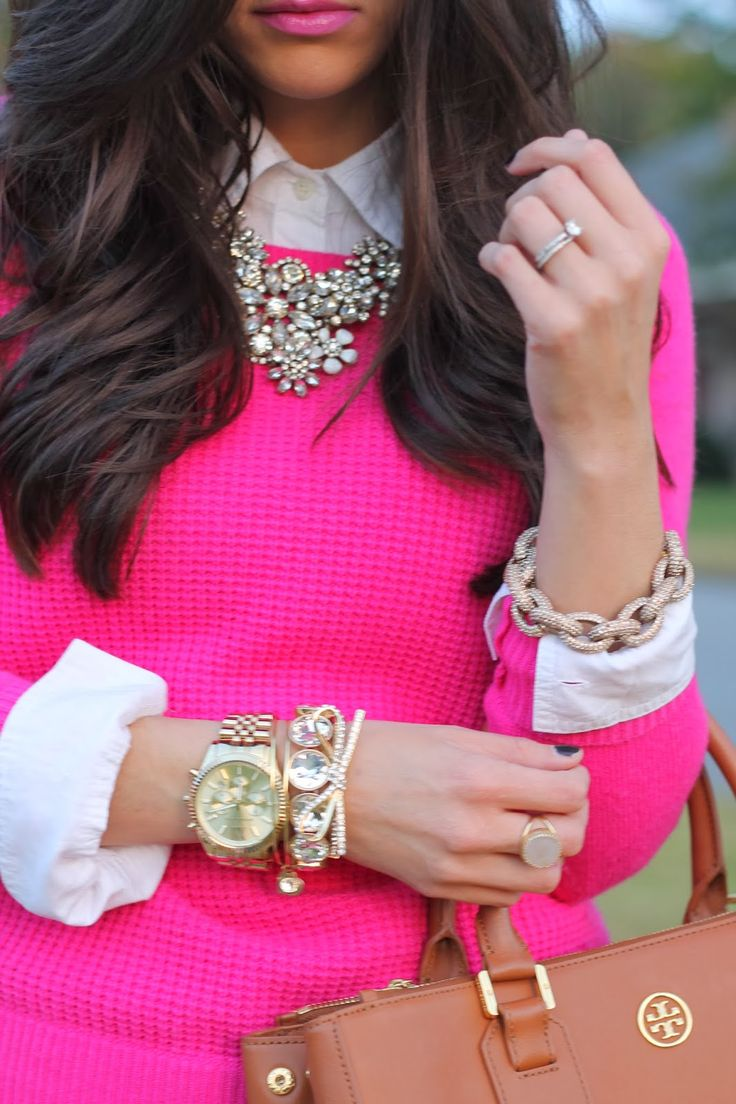 Pink sweater, Tory Burch, and lots of baubles.