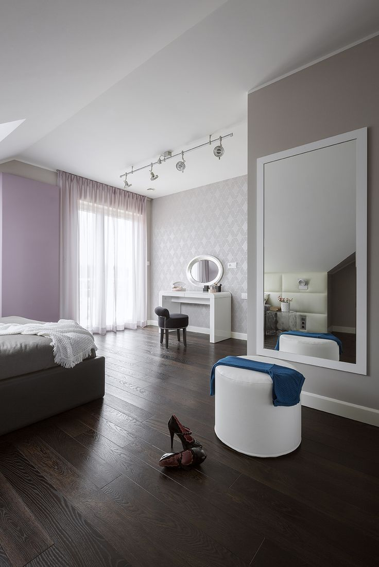 Colourful modern bedroom, bedroom in the attic, leather bed, leather bedhead, white bedhead, dark floor, violet bedroom, grey bedroom, grey wallpaper, modern wallpaper, big mirror, big mirror in bedroom