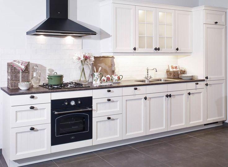 Landelijke keuken in rechte opstelling met klassieke uitstraling door de oven, afzuigkap en bovenkasten met ruitjes. Bekijk meer foto's, gegevens en prijzen op onze website. #klassiek #wit