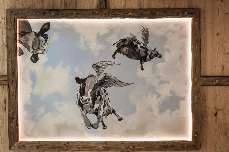 Beim Relaxen auf den Liegeflächen schauen fliegende Kühe herab. Auch an den Wänden und auf dem Boden setzt die Kuhfelloptik Akzente.