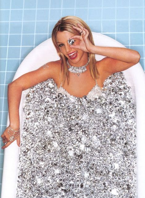 """Speaking of Kitten programming, here's a rare photo of Britney Spears from 2000. She is bathing in diamonds and hiding one eye with a diamond. She also has a diamond butterfly (representing Monarch programming) on her right arm. In MK symbolism, diamonds are the symbol used to identify """"presidential models"""", the highest level of Kitten Programming. Remember when she broke down and shaved her head? She kept screaming she wanted people to stop touching her...c'mon now. This stuff is obvious."""
