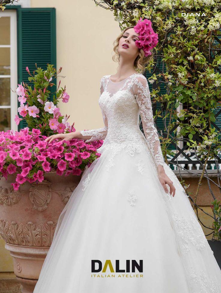 DIANA_Incantevole la sposa con l'abito dal corpino che, sul dorso, presenta un'intrigante scollatura a cuore. Le maniche lunghe sono di pizzo trasparente. Sontuoso lo strascico.