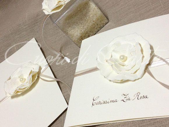 Partecipazioni fatte e scritte a mano, carta martellata avorio, decorate con fiore multistrato in carta e perla, chiusa con nastri. Libretto messa/cerimonia e lancia riso.