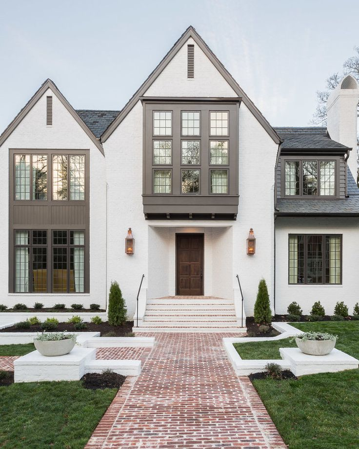 Massive curb appeal for this Modern Tudor. Contrasting paint colors and  lots of windows. Beautiful exterior paint with off white and gray.