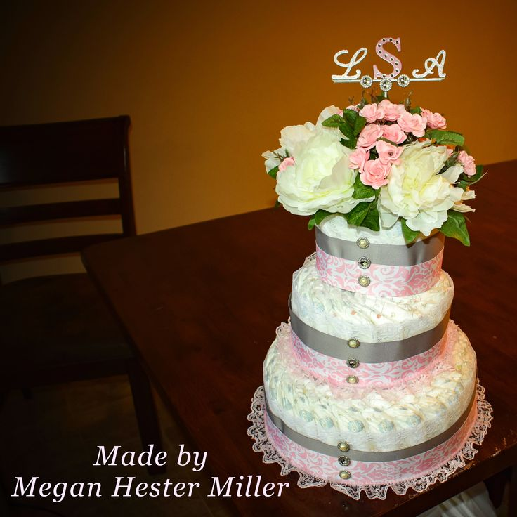 This three tier diaper cake was very simple to make. No hot glue was used for this. Large Rubber bands were used to secure each layer. The ribbon was pinned with the safety pins in the back of the cake so every diaper is usable after the shower. The flower arrangement was made by simply cutting the flowers and sticking in the top. The initials were made with small towel rods and cardboard letters found in the scrapbook section of hobby lobby.
