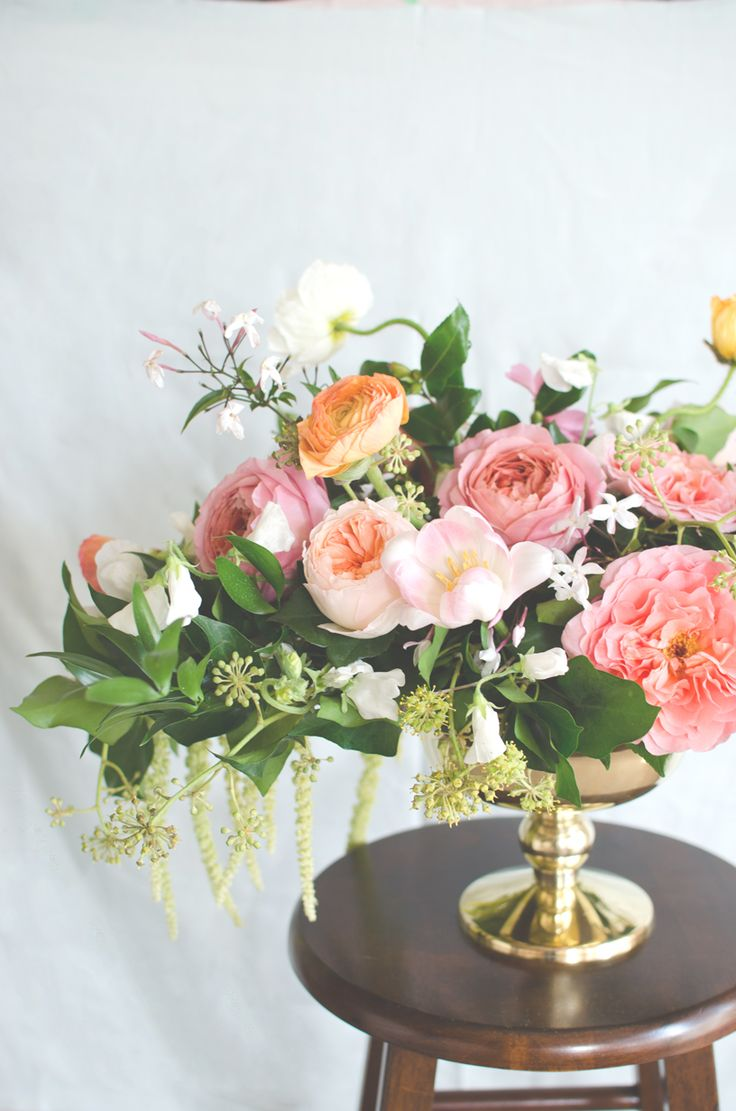 Coral and blush flowers arranged in a classic brass pedestal bowl. | by Gavita Flora #centerpiece