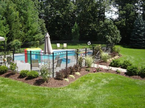 Exterior: Black Iron Fences Around Pool Landscaping Ideas In Some Brick Wall Design Of House With Small Round Pool And Furniture Chairs In Large Yard from 27 Great Pool Landscaping Ideas Designs