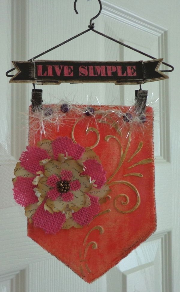 I used a DCWV stencil for the stenciled design, DCWV title and DCWV paper and burlap for the flower. I added beads from DCWV to the center of the flower. I also added DCWV beads to the twine at the top of the wall hanging.