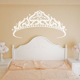 White princes wall decal featuring a large white tiara wall sticker on a beige wall above a white bed headboard in a girl's room.