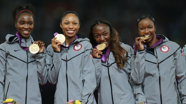 United States pose on the podium during the Victory Ceremony for the women's 4 x 100m Relay