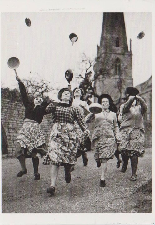 Pancake race on Shrove Tuesday. Love the pinafores, such a practical garment!
