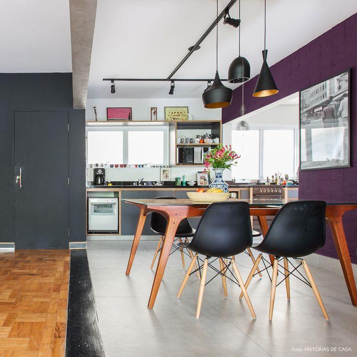Sala de jantar tem parede pintada de roxo, mesa vintage e cadeiras Eames.