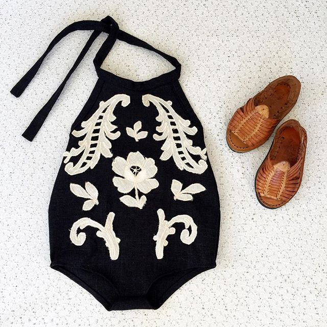 adorable black and white romper for a little girl with brown woven sandals https://presentbaby.com
