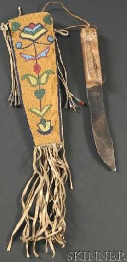 Plains Cree, circa last quarter 19th century, buffalo rawhide form beaded on the front with a polychrome bilateral floral design, tin cone danglers and fringe from the top and bottom, knife with rawhide-covered handle.
