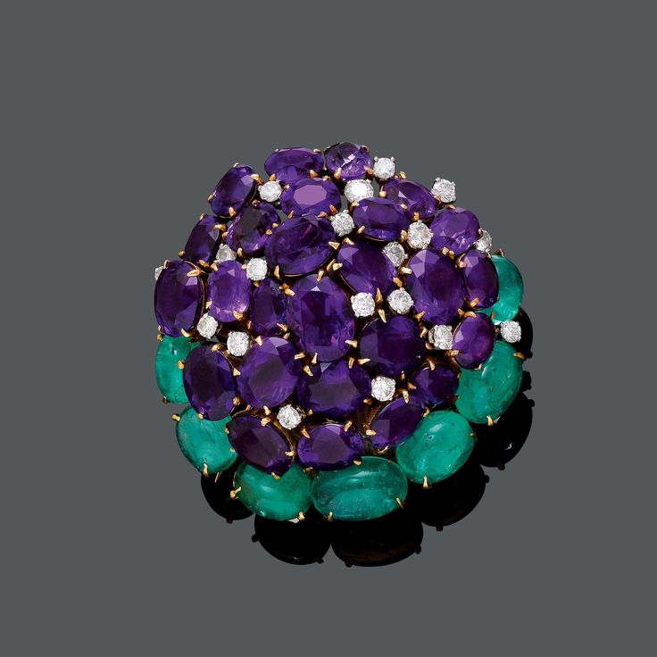 AMETHYST, EMERALD AND DIAMOND BROOCH, ca. 1970. Pink gold 750. Decorative brooch designed as a stylized blossom, set with 26 oval amethysts of different sizes weighing ca. 30.00 ct, 20 brilliant-cut diamonds weighing ca. 1.50 ct, and 7 emerald cabochons weighing ca. 12.00 ct as leaves. Ca. 5.3 x 5 cm.