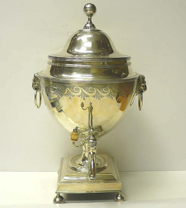 "Georgian Silver Tea Urn  A handsome antique sterling silver samovar with lions mask handles and ivory tap finial. With finely engraved border decoration to both body and lid. The lid has a stag crest to one side and the Scottish family name ""Fraser"" engraved to the other."