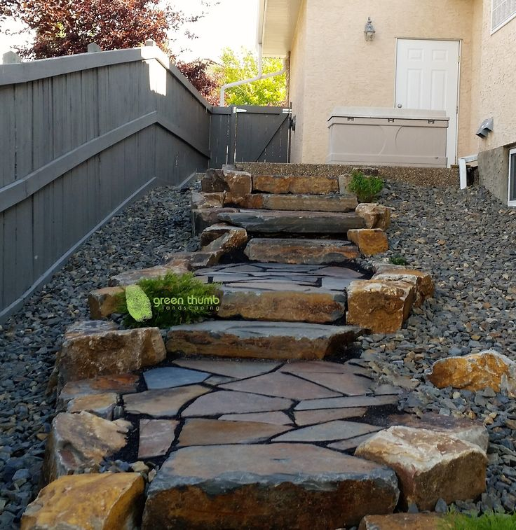 Natural stone stairs with flagstone landings. Boulders work really well to make a boring hill into a functional rustic path.