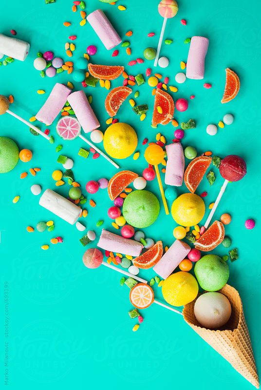 Colorful explosion of candies in ice cream cornet on turquoise background. by Marko Milanovic