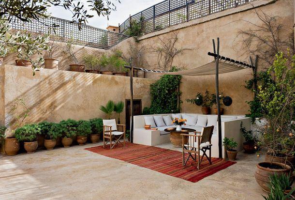 Дом в Марокко. Внутренний дворик. Здесь разумно обыграли высокий забор: его облегчили за счет трельяжной секции, которая бросает во двор неплотную тень и в то же время дает воздуху возможность циркулировать и не застаиваться.