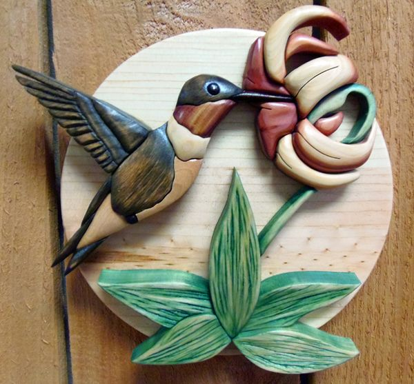 Intarsiais a woodworking technique that uses varied shapes, sizes, and species of wood fitted together to create a mosaic-like picture with an illusion of depth.Intarsiais created through the selec
