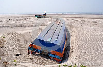 An overturned boat abandoned in a beach in Konkan, along with another boat at a distance and a stray dog.