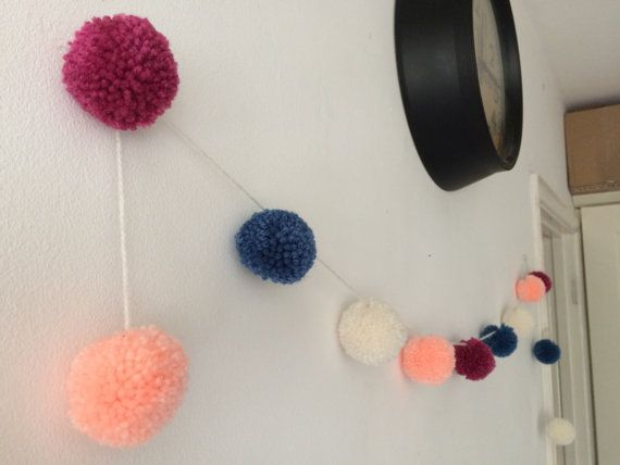 A lovingly handmade pom pom garland with 12 acrylic wool pom poms in a cool colour combination of cream, peach, raspberry and teal. The pom poms are approximately 5cm and the garland is 1.5m long. The pom poms are fixed at even spaces to keep them in place. This would look great in a nursery, living room, bedroom, hanging outdoors or anywhere else you fancy and makes an ideal reusable decoration for parties and events. The garland ends with a pom pom so it can easily be hooked over a pin or…