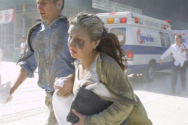 Frightened bystanders flee from the scene of the collapsing twin towers of the World Trade Center in New York City on Sept. 11, 2001.