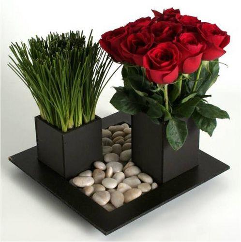 Si tu casa es estilo moderno, en una linda mesa de centro, ¡qué mejor que poner este adorno moderno y lindo! Flores, piedras y el toque de color con esas rosas rojas.