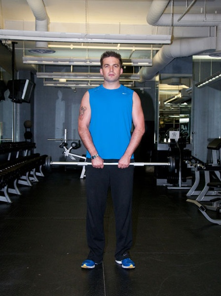 STAREE Rich Tweten: Shoulders Exercise - Upright Row - StartStep 1:Start the exercise by standing tall and hold a barbell with a close, overhand grip.Note: Scroll down to the bottom of this web page and click the image to the left of the one you